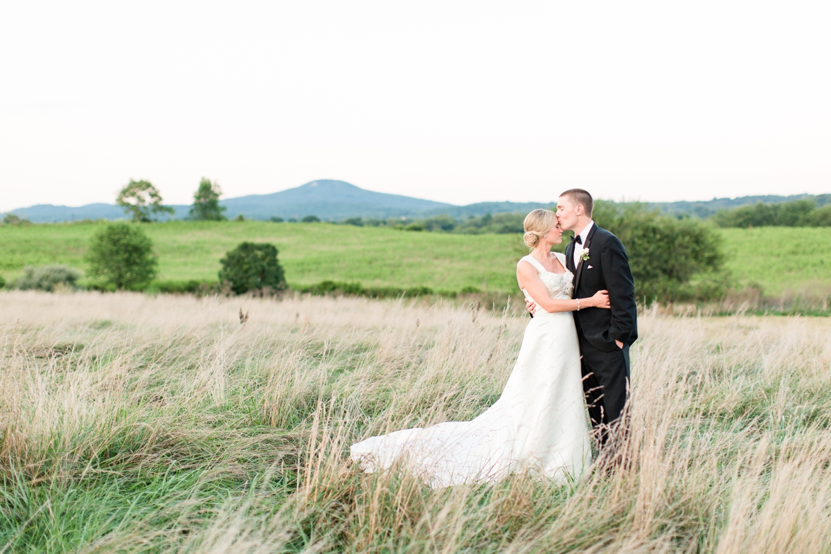 Mountain range Bride and Groom Portraits in an open field of rolling hills. Riverside On the Potomac Barn Wedding Photos.