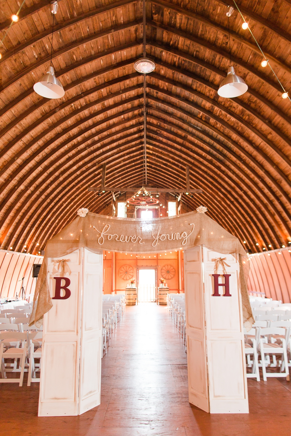 high ceiling, rafter barn wedding ceremony with rustic doors and burlap handmade banner! A Rustic Brandy Hill Farm Wedding in Culpeper, Virginia featuring accents of cranberry and gold! Photos by Katelyn James Photography